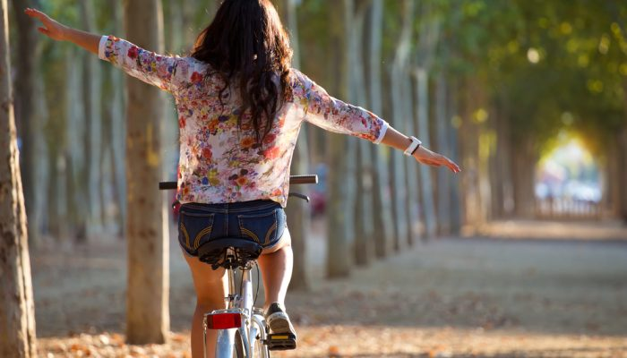 Young woman riding bicycle with her arms wide spread